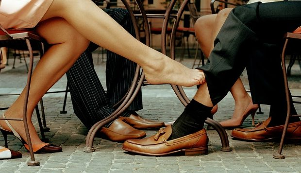 Couples at cafe table, woman's foot touching man's ankle, low section